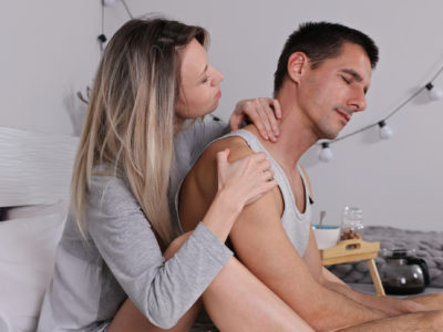 Woman giving massage to her husband. Happy young couple relaxing in bedroom. Love, Relationship, Careness concept